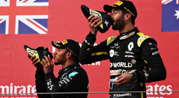 Lewis Hamilton e Daniel Ricciardo brindano con scarpe e champagne sul podio del GP di Imola