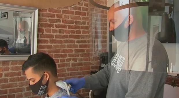 Parrucchiere al tempo del Covid inventa uno scudo mobile per tagliare i capelli