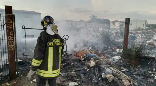 Un pompiere nel campo nomadi di Castel Romano per un incendio