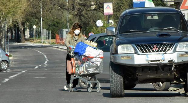 Una signora col carrello della spesa pieno