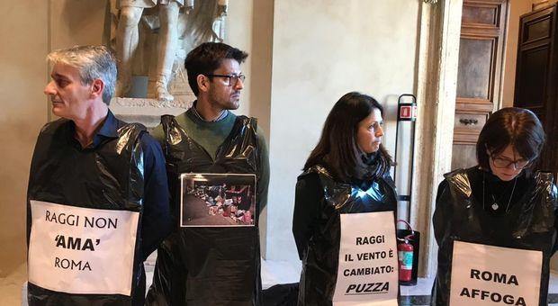 Caos in Consiglio: in Aula con i sacchi dei rifiuti per protesta. Raggi: «A Roma niente discariche». Seduta sospesa