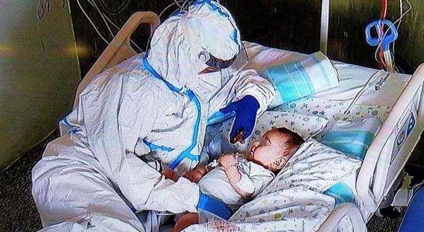 Bimbo di 7 mesi positivo al Covid coccolato da un'infermiera: la foto commuove il web