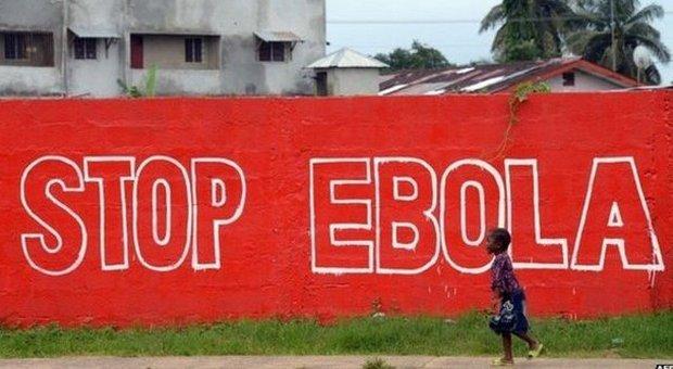 Un bambino in Liberia cammina lungo un enorme striscione che avverte la popolazione