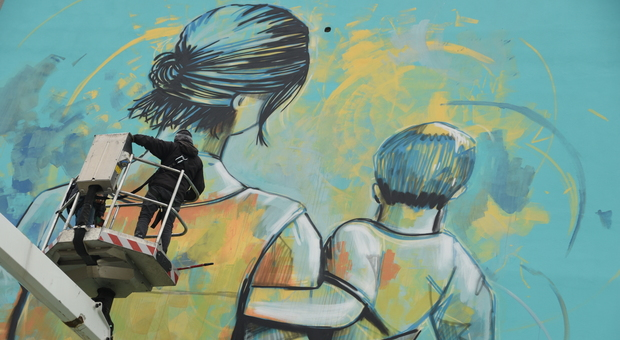 Un momento della lavorazione del murale: in cabina a sinistra c'è l'artista