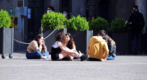 Giovani seduti in piazza del Comune