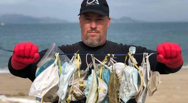 Gary Stokes di Oceans Asia con alcune delle mascherine rinvenute sulle spiagge di Hong Kong. (immagine di Naomi Brannan pubblicata da Oceans Asia su Fb)