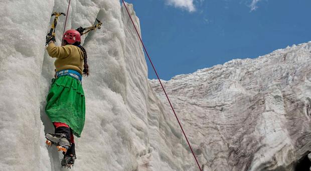 Una delle Cholitas arrampica su una parete di ghiaccio