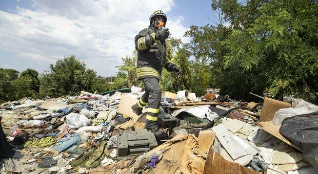 Un vigile del fuoco sopra la discarica durante l'incendio di sabato