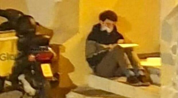 Giovane rider studia a terra sotto un lampione mentre aspetta l'ordine: la foto diventa virale