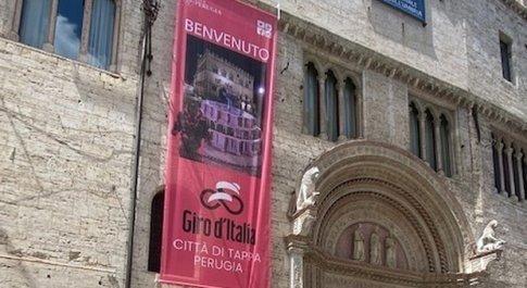 Lo stendardo appeso a palazzo dei Priori annuncia l'arrivo del Giro d'Italia in città