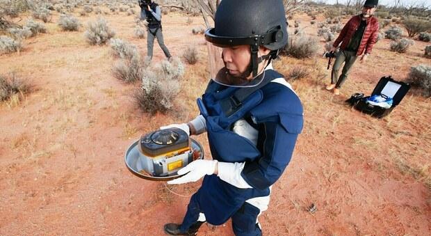 Un ricercatore dell'Agenzia spaziale giapponese raccoglie la capsula contenente il prezioso materiale