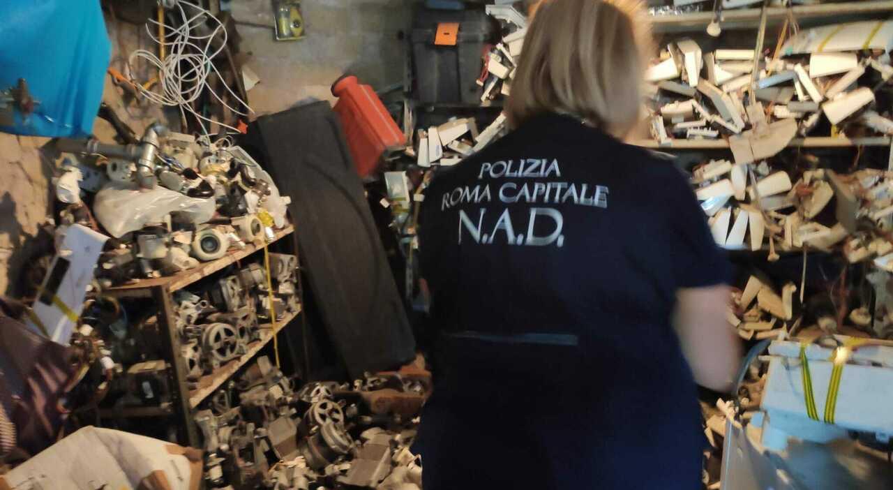 Un agente ispeziona un deposito clandestino di pezzi di elettrodomestici a Tor Bella Monaca