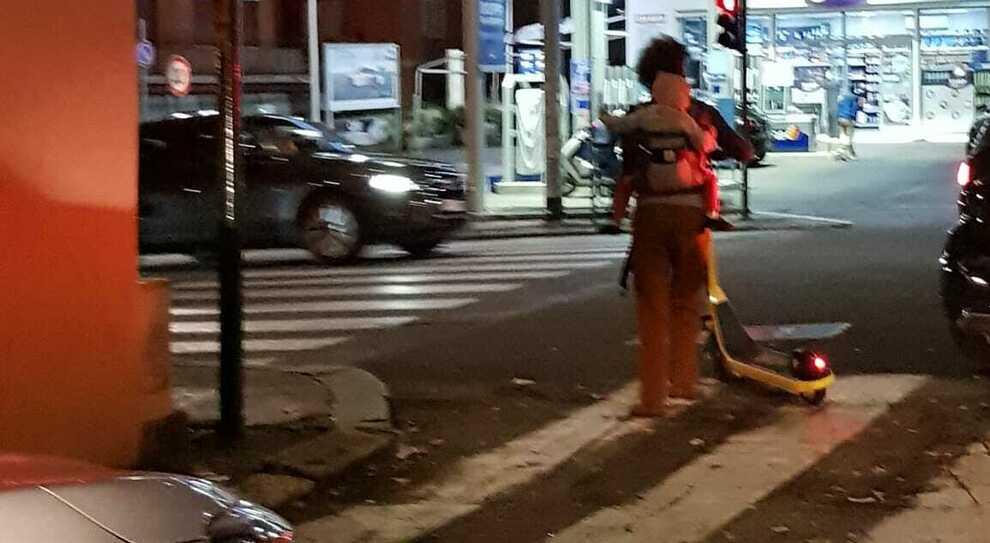 Monopattini, l'ultima follia a Roma: una mamma in giro con il bebè sulle spalle, entrambi senza casco