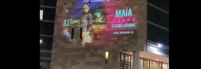 Pubblicità di un sito di escort sulla facciata della Regione Lombardia