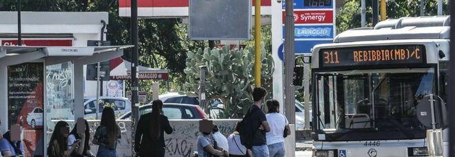 Persone alla fermata di un bus a Roma (foto Ansa)