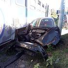 Auto si schianta contro il treno e resta incastrata sotto le rotaie: una donna ferita nello scontro